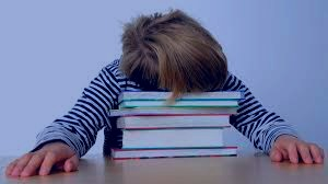 child ovedwhelmrd with stack of books